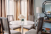 A white tulip-style table with French-inspired dining chairs