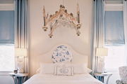 An upholstered headboard and white bedding flanked by a pair of owl lamps