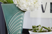 A white hydrangea bloom and a small succulent, each nestled into a ceramic vessel.