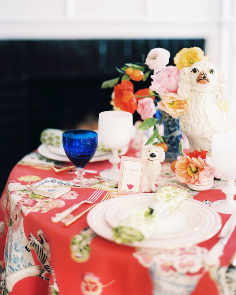 Tablescape - A round table set with vases of flowers and Staffordshire-dog figurines