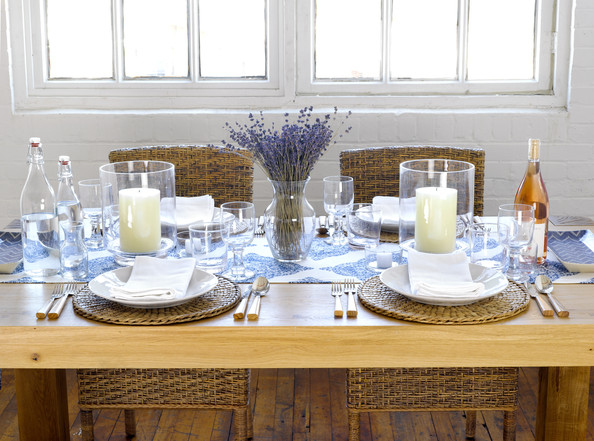 Tablescape - A wooden dining table set with hurricane vases, dried lavender, and a blue-and-white runner