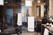 Black marble tile and a glass-enclosed shower