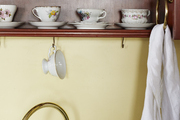 Teacups and saucers on a shelf above a kitchen sink.