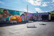White picnic tables against a bright graffiti backdrop in Wynwood Walls