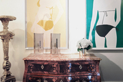 An antique wooden chest paired with contemporary framed art