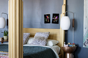 An eclectic bedroom with a gold bed frame and blue walls.