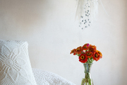 A vase of flowers in a bedroom with white linens