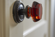 An amber glass and oil-rubbed bronze doorknob in a home designed by BHDM.