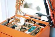 An orange jewelry box draped with necklaces and bracelets