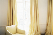 Yellow curtains flanking french doors leading to a balcony