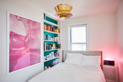 A modern bedroom with pink and teal accents.