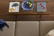 A coffee table beside a Moroccan area rug and a beige sofa