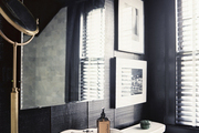A black bathroom with a white pedestal sink and framed black-and-white artwork
