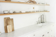This all-white kitchen is decorated with tan accessories.