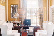 A pair of white wingback chairs and a chinoiserie desk on a patterned orange rug