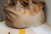 A leather handbag and two-tone accessories on a white tabletop