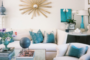 A white couch and chair with a gold starburst mirror