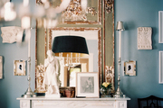 A white mantel decorated with an antique mirror
