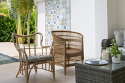 An outdoor space with rattan chairs and tile.