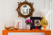 Below a mirror, an orange table topped with vases and other objets