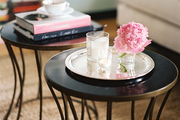 A pair of side tables styled with flowers, candles, and books