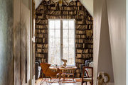 A reading nook with the feel of a library thanks to trompe l'oeil wallpaper