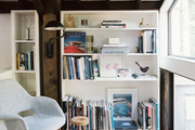 A reading nook with shelves styled with books, art, and accesories