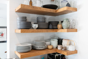 Dishes are arranged on floating wood shelves.