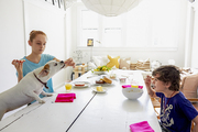 A breakfast table with kids and a dog begging for treats