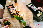 A sushi dinner over a woven table.
