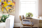 Leopard print chairs and large scale art hangs near white sofa.