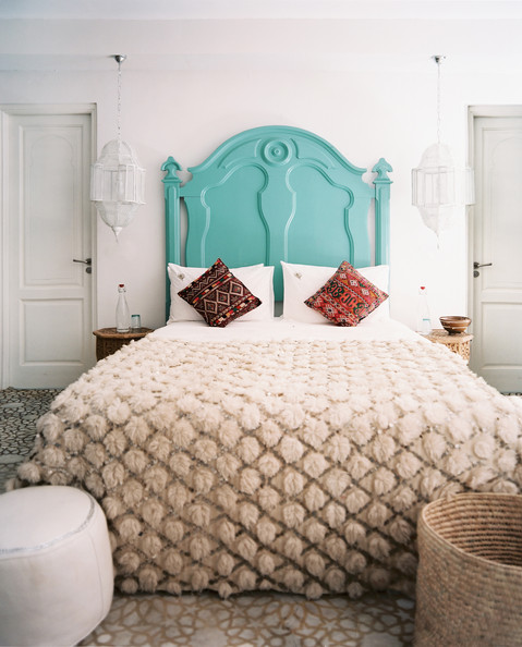 white hanging lantern a bright blue headboard in a neutral bedroom