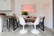 A contemporary dining space with white chairs and metal chairs.