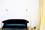A black velvet sofa flanked by two floor lamps