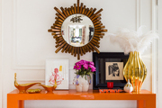 An whimsical entryway vignette of two gnomes beneath a lacquered orange table with assorted objets