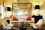 A sitting area with a curved couch and a pair of upholstered chairs surrounding a scallop-edge coffee table