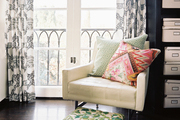 A midcentury chair topped with pillows paired with a floral footstool