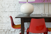 A table lamp and sunburst objets on a table with red midcentury dining chairs