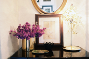 A black console decorated with art, flowers, and an oval mirror