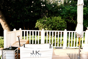 A wooden deck with white railings and oversize lanterns
