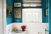 A blue bathroom with a striped roman shade and a corner sink