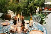 An dining table set for dinner on an outdoor patio
