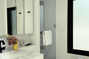 Large Mirrored Cabinet above marble countertop in white tiled bathroom.