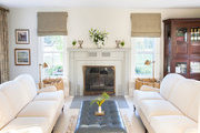 Comfy white couches and cushioned ottoman next to fireplace.