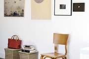 Two oatmeal-color stools serve as perches for books and a bag underneath a wall of artwork