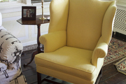 A yellow wingback chair beside a wooden end table