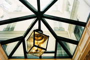A black lantern suspended from a glass ceiling
