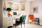 Floral roman shades above a black fretwork chair and a white built-in desk
