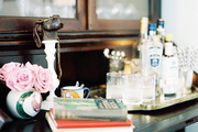 A secretary desk with a tray of bar essentials and glassware