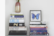 A vase of roses and a framed butterfly sit on stacks of books.